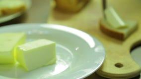 Una donna taglia una fetta di burro e di sbavature su pane per le canape archivi video
