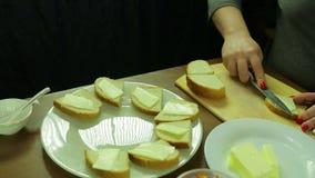 Una donna taglia il burro su pane per le canape con il caviale archivi video