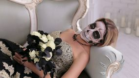 Una donna terrificante con trucco sotto forma di cranio si trova su un retro sofà Halloween stock footage