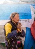 Una donna tibetana prega fotografia stock