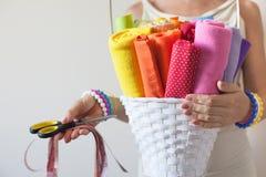 Una donna tiene i tessuti colorati luminosi per il cucito e le forbici Fotografia Stock Libera da Diritti