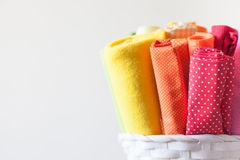 Una donna tiene i tessuti colorati luminosi per il cucito e le forbici Immagini Stock
