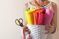 Una donna tiene i tessuti colorati luminosi per il cucito e le forbici Immagine Stock