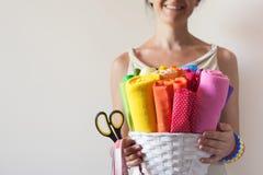 Una donna tiene i tessuti colorati luminosi per il cucito e le forbici Immagini Stock Libere da Diritti
