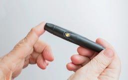 Una donna tiene un lanset e perfora il suo dito per controllare il livello della glicemia Immagine Stock