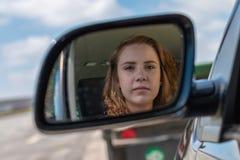 Una donna in un'automobile sta esaminando il retrovisore fotografie stock