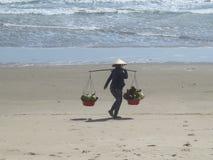 Una donna in un cappello vietnamita sta camminando lungo una spiaggia sabbiosa con due canestri di frutta immagini stock