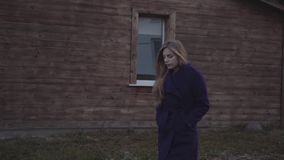 Una donna in un cappotto porpora sta camminando contro lo sfondo della proprietà terriera con una finestra video d archivio