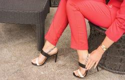 Una donna in un pantsuit che il colore di corallo in tensione si siede in una sedia e che raddrizza il catenaccio sui sandali immagini stock