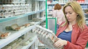 Una donna in un supermercato cammina dopo il canestro dopo i contatori 4k, primo piano, donna sceglie le uova del pollo in a video d archivio
