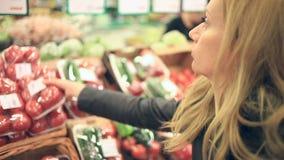 Una donna in un supermercato su uno scaffale di verdure, sulle verdure dei buys e sulla frutta L'uomo sceglie un pomodoro video d archivio