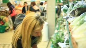 Una donna in un supermercato su uno scaffale di verdure, sulle verdure dei buys e sulla frutta Un uomo sceglie i verdi archivi video