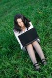 Una donna in un vestito di affari con un computer portatile Fotografie Stock