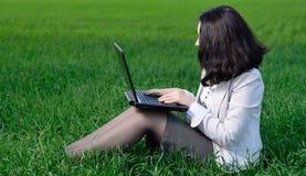 Una donna in un vestito di affari con un computer portatile Immagini Stock