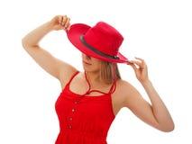 Una donna in un vestito rosso ed in un cappello da cowboy Fotografie Stock