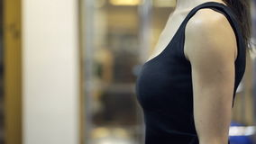 Una donna in una maglia nera pompa le mani con la testa di legno arancio nella palestra stock footage