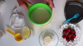 Una donna vaglia la farina per impastare la pasta Accanto alla tavola sono gli ingredienti per la torta archivi video