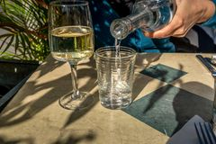 Una donna versa l'acqua in un vetro accanto ad un vetro di vino bianco i Fotografia Stock