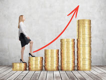 Una donna in vestiti convenzionali sta andando consumare scale che sono fatte delle monete dorate La freccia rossa è attinta la p Fotografia Stock