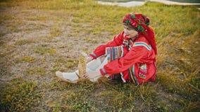 Una donna in vestiti pieghi russi che mettono sulle scarpe della rafia - sedendosi sul campo archivi video