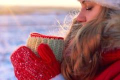 Una donna, in vestiti rossi caldi, beve il tè o il caffè caldo nella natura nel tramonto caldo Immagini Stock Libere da Diritti