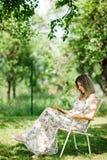 Una donna in vestito dal fiore ? libro di lettura nel giardino - sedia di campo immagine stock