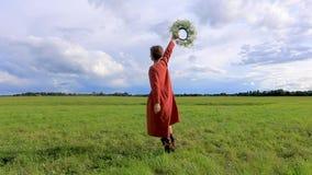 Una donna in vestito nazionale sta filando con una corona dei fiori contro il contesto di un cielo tempestoso Movimento lento archivi video