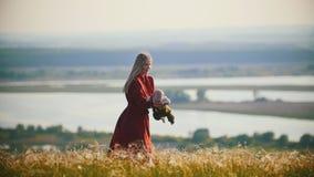 Una donna in vestito rosso che gioca con il suo poco bambino sul campo su un fondo del fiume stock footage