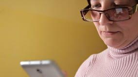 Una donna in vetri che scrive un messaggio sul suo smartphone nuovissimo mentre sedendosi sullo strato con un cuscino bianco a ca stock footage