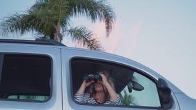Una donna viaggia lungo un'isola tropicale e esamina la distanza tramite il binocolo archivi video