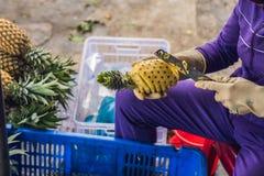 Una donna vietnamita sta pulendo l'ananas nel mercato vietnamita Concetto asiatico di cucina Immagine Stock Libera da Diritti