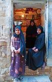 Una donna yemenita e due ragazze yemeniti in Thula, villaggio, cisterna, porta di legno, Yemen Fotografie Stock