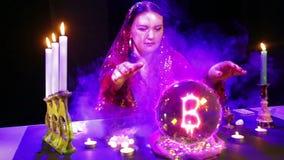 Una donna zingaresca in un salone magico nei soffi delle congetture del fumo su una sfera di cristallo e su un segno del bitcoin  video d archivio
