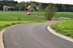 Una doppia curvatura nella strada fra i campi Fotografia Stock