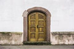 Una doppia porta di legno con una entrata di pietra immagini stock