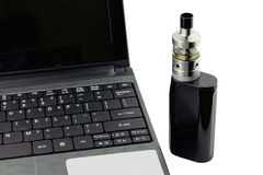 Una e-sigaretta che si siede accanto ad un computer portatile Fotografie Stock Libere da Diritti