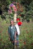 Una edad 68 de Kohinur del vendedor ambulante de calle del pueblo, vendiendo las flores de papel coloridas, Dacca, Bangladesh