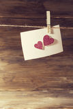 Una ejecución blanca de la hoja de papel en pinza en la hoja de corazones brillantes rosados delicados, un lugar a la prueba Imagen de archivo