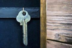 Una ejecución dominante en un gancho de oro en un tenedor de la llave de la pared en fondo de madera rústico Hipoteca, seguro, co fotografía de archivo libre de regalías