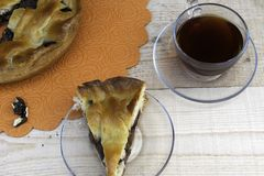 Una empanada, una rebanada de empanada de manzana llenada de las cerezas y de las nueces, una taza de té y un puñado de nueces pe imágenes de archivo libres de regalías