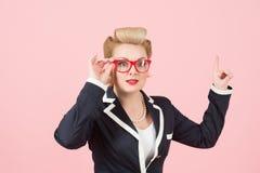 Una empresaria en vidrios rojos señala para arriba en fondo rosado La señora en chaqueta que considera el anuncio y los puntos co fotografía de archivo