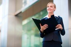 Una empresaria hermosa que sostiene un sujetapapeles Fotografía de archivo libre de regalías