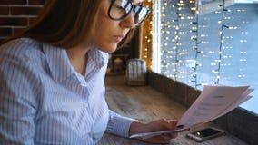 Una empresaria joven trabaja en un café y mira los documentos metrajes