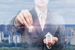 Una empresaria o un agente inmobiliario está llevando a cabo llaves y el modelo de la casa imagen de archivo libre de regalías