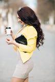 Una empresaria que habla vía el teléfono móvil y que sostiene una taza de café Muchacha elegante delgada joven en la ropa brillan Foto de archivo