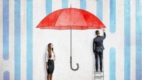 Una empresaria se coloca cerca de una pared donde un hombre de negocios extrae un paraguas rojo gigante que los cubre de la lluvi foto de archivo