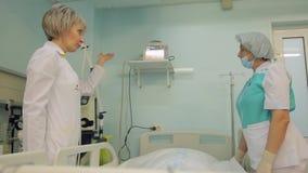 Una enfermera de sexo femenino y un doctor de sexo femenino visitan a un paciente y discuten su condición 4K metrajes