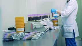 Una enfermera explora códigos de barras en las botellas de las muestras de sangre, entonces las coloca sobre un estante especial almacen de video