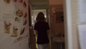 Una enfermera joven toma un documento de papel y lo trae al cuarto siguiente al doctor almacen de metraje de vídeo