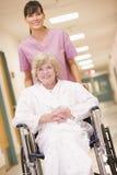 Una enfermera que empuja a una mujer mayor en un sillón de ruedas Foto de archivo libre de regalías